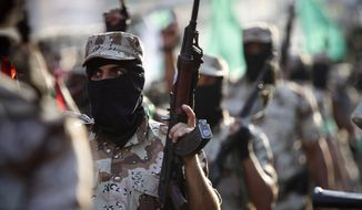 FILE - In this Nov. 14, 2013 file photo, masked Palestinian members of the military wing of Hamas carry their weapons while chanting slogans during a parade to mark the anniversary of a 2012 battle against Israel in Gaza City. Hamas is entering Egyptian-brokered talks with Israel over a new border regime for blockaded Gaza having lost hundreds of fighters, two-thirds of its arsenal of rockets, and its attack tunnels.(AP Photo/Adel Hana, File)