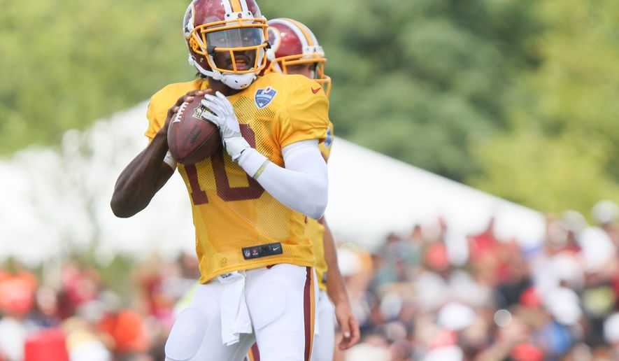 Washington Redskins QB Robert Griffin III works out before an NFL Football training camp scrimmage of New England Patriots and Washington Redskins in Richmond, Va., Tuesday, Aug. 5, 2014. (AP Photo/Skip Rowland)
