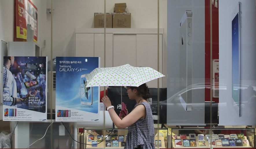 A woman walks by advertisement posters of Samsung Electronics' Galaxy S5, Apple's iPhone 5s and iPad Air at a mobile phone shop in Seoul, South Korea, Wednesday, Aug. 6, 2014. Samsung and Apple Inc. have agreed to end all patent lawsuits between each other outside the U.S. in a step back from three years of legal hostilities between the world's two largest smartphone makers. (AP Photo/Ahn Young-joon)