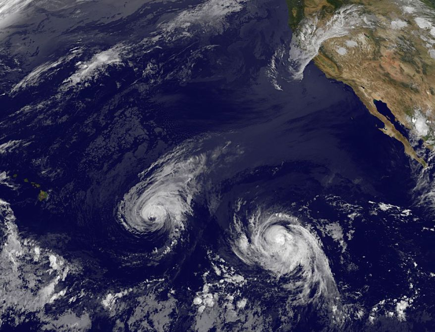 This image provided by NOAA taken Wednesday Aug. 6, 2014 shows Hurricane Iselle, center, and tropical storm Julio, right. Though it's not clear how damaging the storms could be, many in Hawaii aren't taking any chances as they wait for Hurricane Iselle to make landfall later this week and Tropical Storm Julio potentially hitting a few days later. (AP Photo/NOAA)