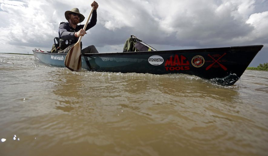 Joshua Ploetz, a former Marine, canoes in the Mississippi River near Venice, La., Sunday, July 27, 2014. Ploetz, who has been dealing with post-traumatic stress disorder, canoed the entire Mississippi River. The trip to the mouth of the river at the Gulf of Mexico would take 69 days, about 50 of them spent paddling. But Ploetz said he needed every inch of the more than 2,500-mile river to paddle away the demons of the war, or at least calm them a bit. (AP Photo/Gerald Herbert)