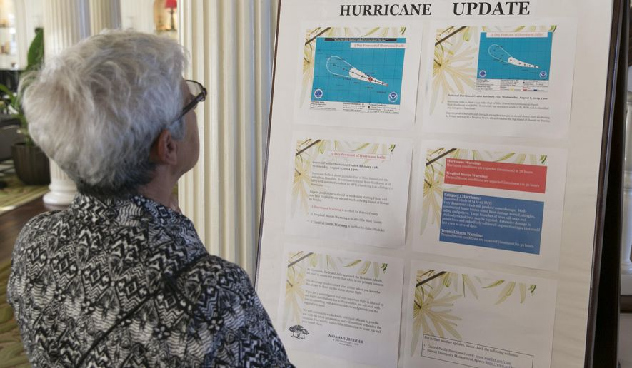 Tourist Denise Newland of New Zealand reads a hurricane update in the lobby of a hotel in Waikiki in Honolulu on Thursday, Aug. 7, 2014. With Iselle, Hawaii is expected to take its first direct hurricane hit in 22 years. Tracking close behind it is Hurricane Julio. (AP Photo/Marco Garcia)