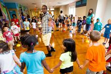 Jonathan Cogdell (center) leads an activity with 6-year-olds during the last day of vacation Bible school.