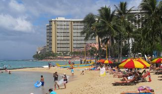People lounge on Waikiki's beaches in Honolulu on Wednesday, Aug. 6, 2014. Hawaii residents prepared for what could be the first hurricane to hit the state in more than 20 years as weather officials said an approaching storm appears to have strengthened and will likely maintain its speed as it heads toward the islands. (AP Photo/Audrey McAvoy)