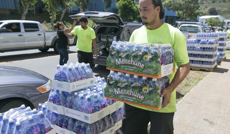 A worker at the Menehune Water Company carries bottle of water to waiting customers, Thursday, Aug. 7, 2014, in Aiea, Hawaii.  Hawaii is bracing for two back to back hurricanes, Iselle and Julio, which are on course to hit the Islands.  Bottles of water are quickly disappearing off shelves in Hawaii causing many people to line up for several hours to purchase water directly from the company.  (AP Photo/Marco Garcia)