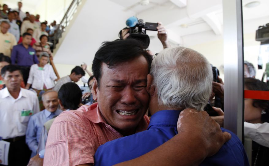 Cambodian former Khmer Rouge survivors, Soum Rithy, left, and Chum Mey, right, embrace each other after the verdicts were announced, at the U.N.-backed war crimes tribunal in Phnom Penh, Cambodia, Thursday, Aug. 7, 2014. Three and a half decades after the genocidal rule of Cambodia's Khmer Rouge ended, the tribunal on Thursday sentenced two top leaders of the former regime to life in prison on war crimes charges for their roles during the country's 1970s terror. (AP Photo/Heng Sinith)