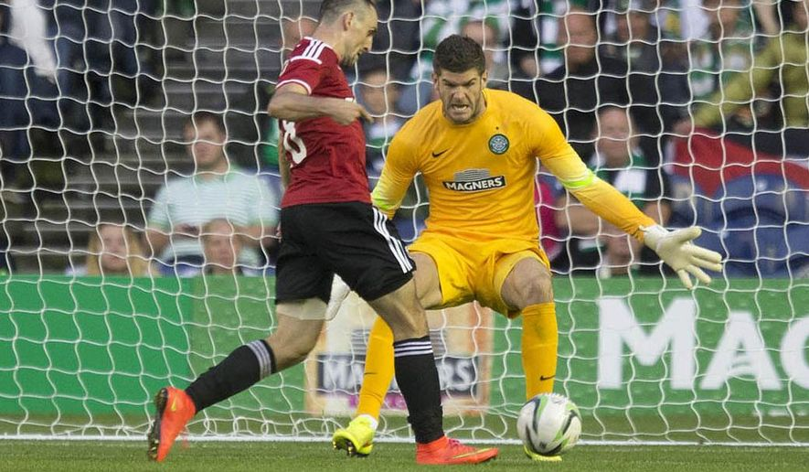 Legia Warsaw's Michal Kucharczyk, left, scores past Celtic's Fraser Foster during their Champions League qualifying soccer match at Murrayfield, Edinburgh, Wednesday Aug. 6, 2014. (AP Photo/PA, Jeff Holmes) UNITED KINGDOM OUT  NO SALES  NO ARCHIVE