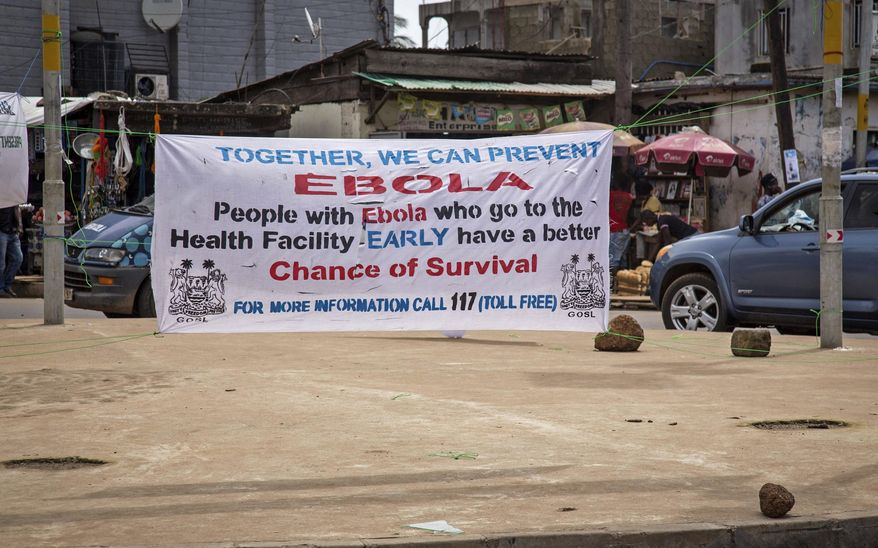 A banner encouraging people suffering from Ebola to go immediately to a health center for treatment is seen on a sidewalk in the city of  Freetown, Sierra Leone, Thursday, Aug. 7, 2014. While the Ebola virus outbreak has now reached four countries, Liberia and Sierra Leone account for more than 60 percent of the deaths, according to the World Health Organization. The outbreak that emerged in March has claimed at least 932 lives. (AP Photo/Michael Duff)