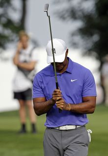 Tiger Woods reacts to his putt on the 10th hole during the first round of the PGA Championship golf tournament at Valhalla Golf Club on Thursday, Aug. 7, 2014, in Louisville, Ky. (AP Photo/John Locher)