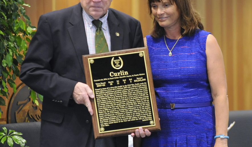 Hall of Fame committee chairman Edward Bowen, left, presents a plaque to Barbara Banke, owner of Stonestreet Farm, as Curlin is inducted into the National Thoroughbred Racing Hall of Fame on Friday, Aug. 8, 2014,  in Saratoga Springs, N.Y.  (AP Photo/Tim Roske)
