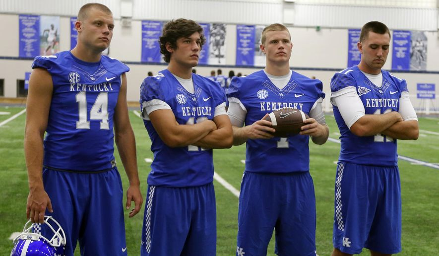 Kentucky starting quarterback hopefuls, from left, Patrick Towles, Reese Phillips, Drew Barker and Max Smith wait to have their photo taken during the team's NCAA college football media day, Friday, Aug. 8, 2014, in Lexington, Ky. (AP Photo/James Crisp)