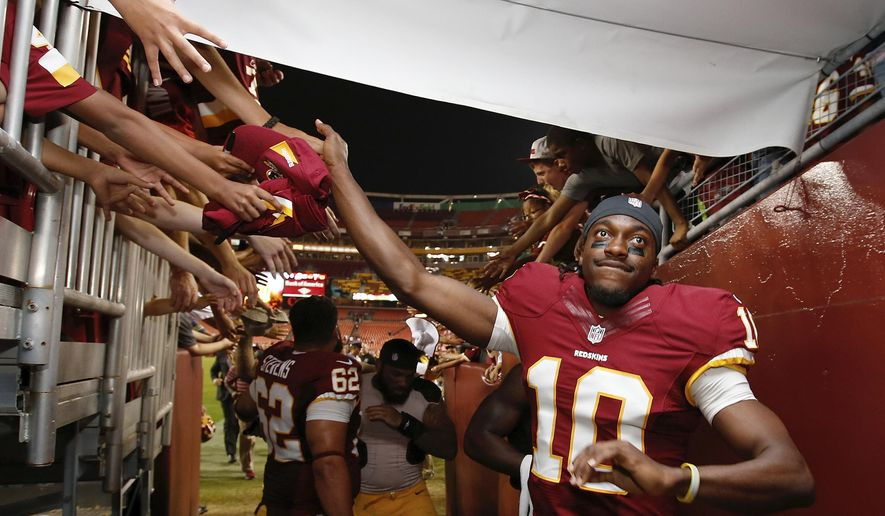 Washington Redskins quarterback Robert Griffin III reaches for fans' hands as he leaves the field after an NFL football preseason game against the New England Patriots in Landover, Md., Thursday, Aug. 7, 2014. The Redskins defeated the Patriots 23-6. (AP Photo/Alex Brandon)