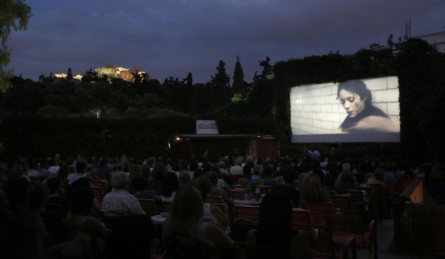 "In this July 23, 2014 photo, people watch the movie ""The Immigrant "" at the Thisio outdoor summer cinema as the Ancient Acropolis is seen lit up in the background. Cine Thisio is one of the oldest open-air movie theaters in Athens, built in 1935. (AP Photo/Petros Giannakouris)"