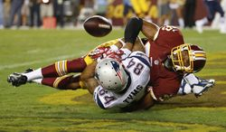 New England Patriots wide receiver Brian Tyms loses control of the ball in the end zone on a hit from Washington Redskins defensive back Chase Minnifield during the second half of an NFL football preseason game in Landover, Md., Thursday, Aug. 7, 2014. (AP Photo/Alex Brandon)
