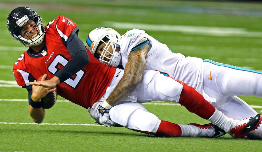 Atlanta Falcons quarterback Matt Ryan is brought down by Miami Dolphins linebacker Koa Misi, but the play was negated by a Miami penalty during the first quarter of an NFL preseason football game Friday, Aug. 8, 2014, in Atlanta. (AP Photo/Atlanta Journal Constitution, Curtis Compton)