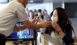 A South Korean quarantine officer, left, checks body temperature of a passenger against possible infections of Ebola virus at the Incheon International Airport in Incheon, South Korea, Friday, Aug. 8, 2014. South Korea has been stepping up monitoring of its citizens returning from trips to West Africa and other areas affected by the deadly Ebola virus. (AP Photo/Yonhap, Choe Jae-koo)  KOREA OUT