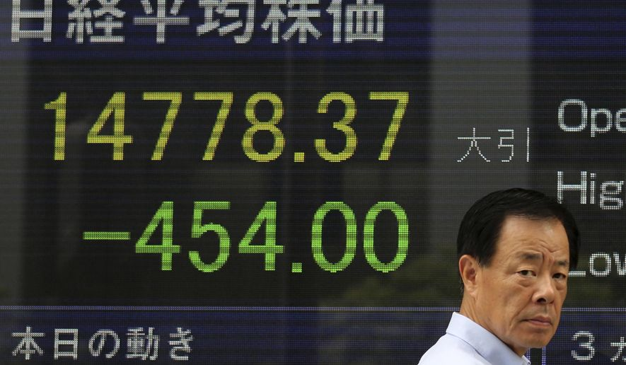 A man walks past an electronic stock board of a securities firm in Tokyo as the 225-issue Nikkei Stock Average dived 454.00 points, or 2.98 percent, and finished at 14,778.37, hitting a two-month low. Asian stocks sank Friday as jitters over the crises in Iraq and Ukraine escalated but Chinese stocks rose after trade figures showed surprisingly strong growth in exports. (AP Photo/Eugene Hoshiko)