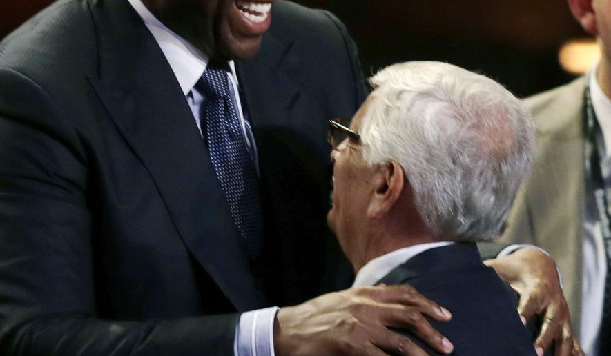Former Los Angeles Laker Magic Johnson, left, embraces former NBA Commissioner David Stern prior to the induction ceremony for the Basketball Hall of Fame in Springfield, Mass., Friday, Aug. 8, 2014. Stern will be presented by Hall of Fame players Larry Bird, Bob Lanier and Johnson. (AP Photo/Charles Krupa)