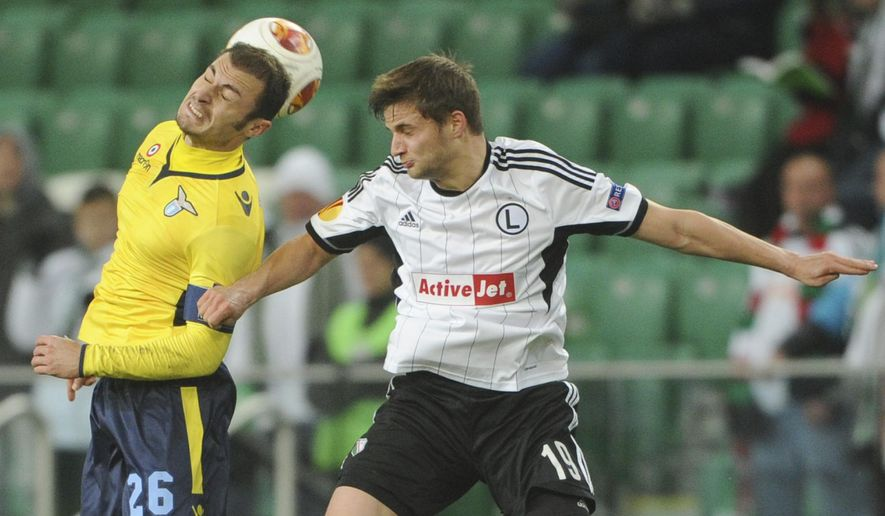 FILE -In this Thursday, Nov. 28, 2013 file photo Legia Warsaw's Bartosz Bereszynski   Lazio's Stefan Radu, left, challenge for the ball during their Europa League Group J soccer match between Legia Warszawa and Lazio Rome  in Warsaw, Poland. UEFA said Friday Auc. 8, 2014, Scottish side Celtic has been reinstated to the Champions League playoffs after qualifying-round opponent Legia Warsaw was punished for fielding Bartosz Bereszynski  an ineligible player. Legia won the third-round match 6-1 on aggregate after following up a 4-1 victory in the first leg with a 2-0 win at Murrayfield on Wednesday. But the Polish side brought on Bartosz Bereszynski as an 86th-minute substitute in the second leg, even though he was suspended for the game. (AP Photo/Alik Keplicz, File)