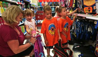 """""""She's the one who always needs something extra,"""" said mother Jill Schwartz, who listens to her daughter Molly, left,  make a pitch for her mom to buy her a clip-on dog ornament for her backpack while shopping for school lunch boxes and packs with her quadruplets on Tuesday, July 22, 2014, at Target.  """"It's fun to watch them each grow into their own person,"""" said Schwartz. The quads stand, from left to right  Molly, Cole, Meghan and Kurt. (AP Photo/St. Louis Post-Dispatch, Laurie Skrivan)"""