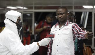 In this Aug. 6, 2014, file photo, a Nigerian port health official uses a thermometer on a worker at the arrivals hall of Murtala Muhammed International Airport in Lagos, Nigeria. (AP Photo/Sunday Alamba, File) ** FILE **