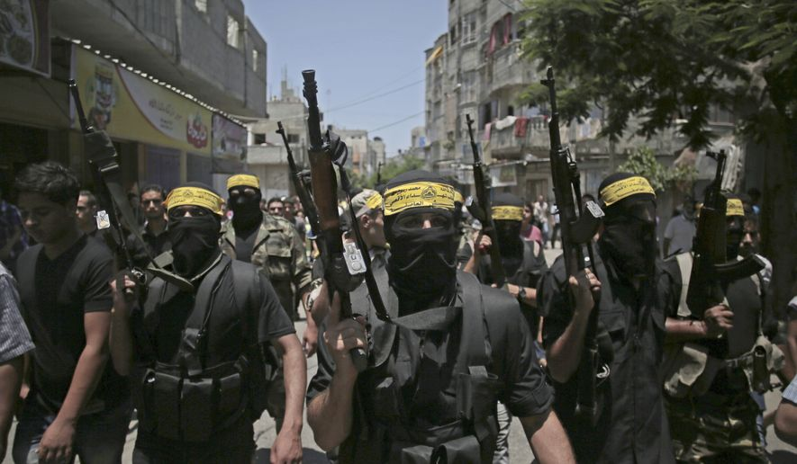 FILE - In this file photo taken Monday, July 7, 2014, masked militants march with guns as they attend the funeral of the two Fatah militants, Marwan Sleem and Mazin Al-Jarba, who were killed by an Israeli airstrike, in Bureij refugee camp, central Gaza Strip. In the grisly math of the Israel-Hamas war, conflicting counts of combatants and civilians killed in Gaza are emerging - with the ratio perhaps more important to shaping international opinion of the monthlong conflict than any final toll. U.N. researchers and local rights groups say three-fourth of some 1,900 dead were civilians, while the Israeli military estimates the split is closer to 50-50. Those doing the tallies use different methods and standards to make that all important determination of who is a civilian. (AP Photo/Khalil Hamra, File)