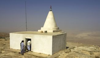 FILE - In this Sept. 18, 2005 file photo, Yazidi men enter a shrine at the top of Mount Sinjar, 250 miles (404 kilometers) northwest of Baghdad, Iraq. Iraqis on Friday, Aug. 8, 2014 welcomed the U.S. airlift of emergency aid to thousands of people who fled to the mountains to escape Islamic extremists and called for greater intervention, as U.S. warplanes struck the militants for the first time. Cargo planes dropped parachuted crates of food and water over an area in the mountains outside Sinjar, where thousands of members of the Yazidi minority where sheltering, according to witnesses in the militant-held town, who asked not to be identified for security reasons.(AP Photo/Jacob Silberberg, File)