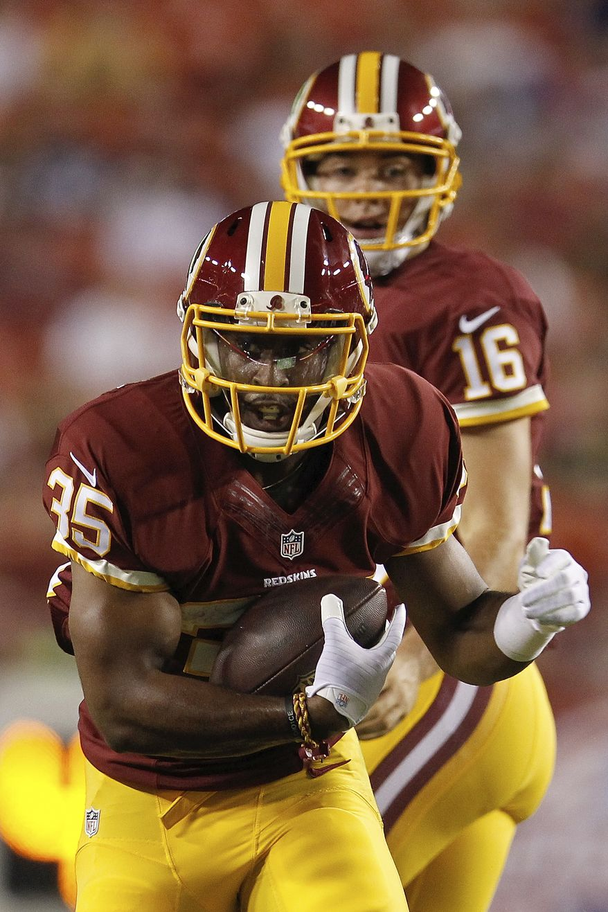Washington Redskins running back Lache Seastrunk carries the ball during the second half of an NFL football preseason game against th eNew England Patriots in Landover, Md., Thursday, Aug. 7, 2014. (AP Photo/Connor Radnovich)