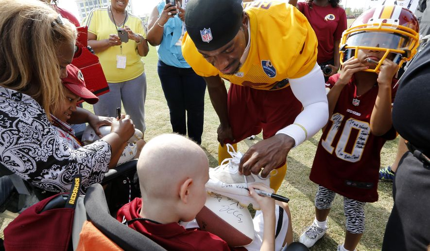 After signing autographs, Redskins quarterback Robert Griffin III, asks for a favor in return, he has Vincent Silver, Jr., left, and Evan Washo sign his shoes after training camp practice Saturday, Aug. 9, 2014 in Richmond, Va..  At right, Griffin's niece Jania Hope Moton wears his helmet. (AP Photo/ Richmond Times-Dispatch, Dean Hoffmeyer)