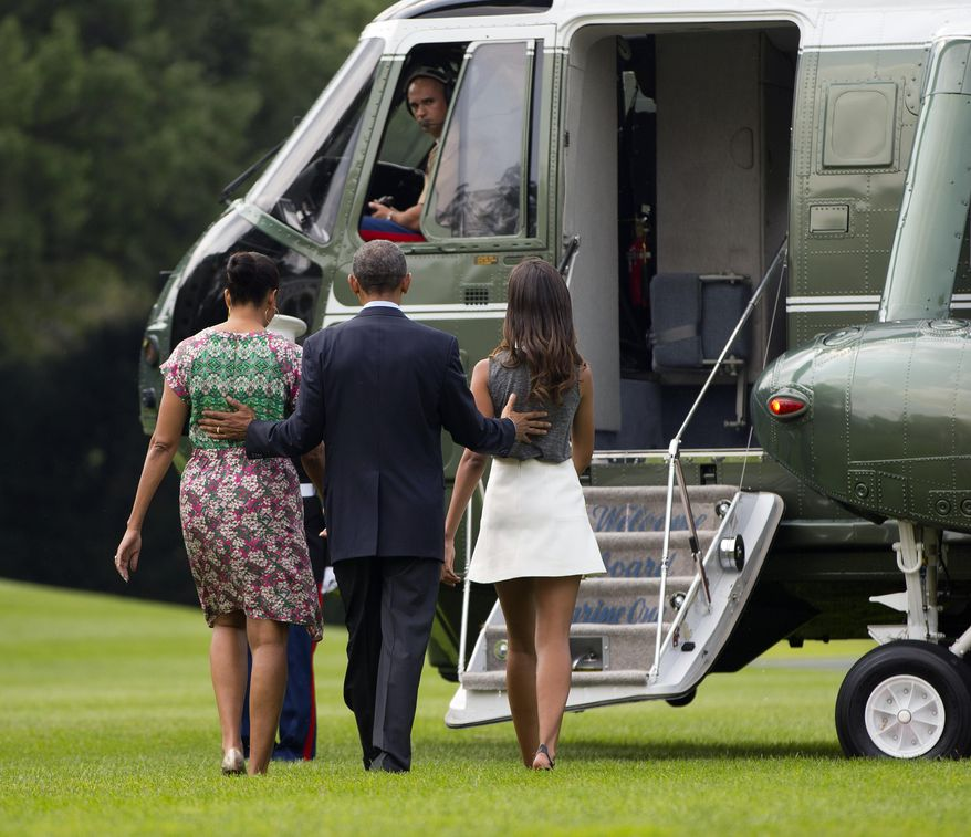 President Barack Obama, center, walks with first lady Michelle Obama, left, and their daughter Malia, right, as they board Marine One helicopter on the South lawn of the White House in Washington, Saturday, Aug. 9, 2014, en route to a family vacation in Martha's Vineyard. The president is doing something unusual with his summer vacation: He'll come back to Washington midway through the getaway to attend White House meetings. (AP Photo/Pablo Martinez Monsivais)