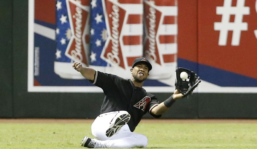 Arizona Diamondbacks' Alfredo Marte makes a sliding catch in the seventh inning to rob the Colorado Rockies' Charlie Blackmon of a hit during a baseball game, Saturday, Aug. 9, 2014, in Phoenix. (AP Photo/Darryl Webb)