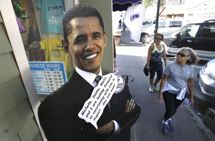 Passers-by walk near a cut-out of President Barack Obama, left, outside a shop Saturday, Aug. 9, 2014, in Oak Bluffs, Mass., on the island of Martha's Vineyard. President Obama and his family are returning to the island off the Massachusetts mainland Saturday. The president is doing something unusual with his summer vacation on Martha's Vineyard: He'll come back to Washington midway through the getaway to attend White House meetings. (AP Photo/Steven Senne)