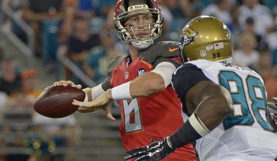 Tampa Bay Buccaneers quarterback Mike Glennon, left, throws a pass as he is pressured by Jacksonville Jaguars defensive end Chris Smith (98) during the first half of an NFL preseason football game in Jacksonville, Fla., Friday, Aug. 8, 2014. (AP Photo/Phelan M. Ebenhack)