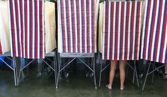 A voter can be seen in a voting booth Saturday, Aug. 9, 2014 in Honolulu.  Despite the rains and winds from Tropical Storm Iselle that pounded the state Friday, Hawaii will hold primary elections today.  (AP Photo/Marco Garcia)