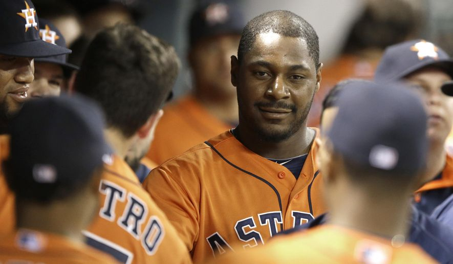 Houston Astros' Chris Carter, center, is welcomed back to the dugout after hitting a solo home run against the Texas Rangers in the fifth inning of a baseball game Friday, Aug. 8, 2014, in Houston. (AP Photo/Pat Sullivan)