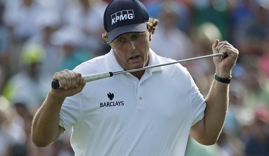 Phil Mickelson reacts to his missed eagle putt on the 18th hole during the third round of the PGA Championship golf tournament at Valhalla Golf Club on Saturday, Aug. 9, 2014, in Louisville, Ky. (AP Photo/Mike Groll)