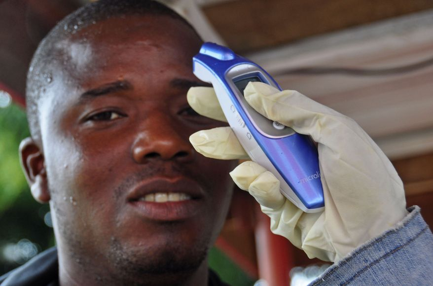 A man's temperature is measured before he is allowed into a business center, as fear of the deadly Ebola virus spreads through the city of Monrovia, Liberia, Saturday, Aug. 9, 2014. Over the decades, Ebola cases have been confirmed in 10 African countries, including Congo where the disease was first reported in 1976. But until this year, Ebola had never come to West Africa. (AP Photo/Abbas Dulleh)