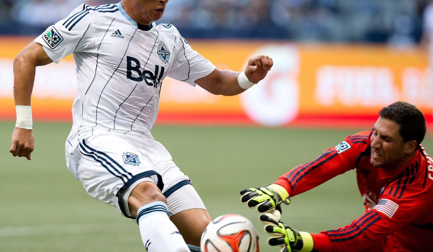 Vancouver Whitecaps' Erik Hurtado, left, is stopped by Sporting Kansas City goalkeeper Andy Gruenebaum during the first half of an MLS soccer game in Vancouver, British Columbia, on Sunday, Aug. 10, 2014. (AP Photo/The Canadian Press, Darryl Dyck)