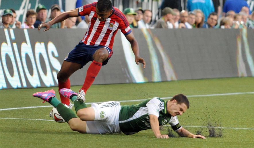 Portland Timbers midfielder Will Johnson (4) slides in and gets the ball away from Chivas USA midfielder Oswaldo Minda, top, during the first half of an MLS soccer game in Portland, Ore., Saturday, Aug. 9, 2014. (AP Photo/Steve Dykes)