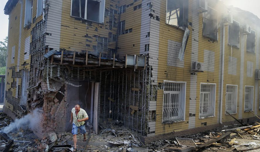 "A man runs out of the destroyed building after shelling in Donetsk, eastern Ukraine on Sunday. Fighting raged Sunday in the city despite a request from the pro-Russian rebels there for a cease-fire to prevent a ""humanitarian catastrophe."" (Associated Press)"