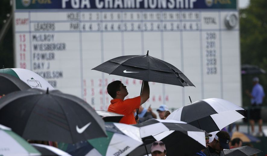A golf fan puts up an umbrella during a rain delay during the final round of the PGA Championship golf tournament at Valhalla Golf Club on Sunday, Aug. 10, 2014, in Louisville, Ky. (AP Photo/Mike Groll)
