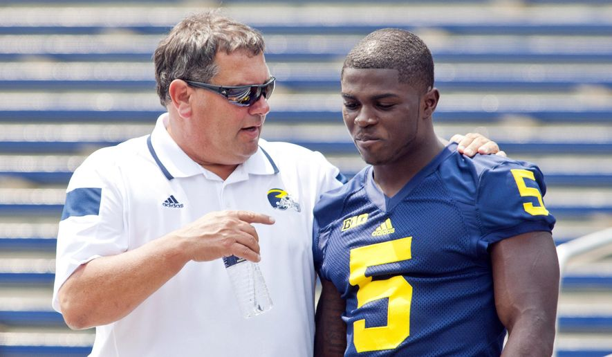 Michigan head coach Brady Hoke, left, speaks with freshman cornerback Jabrill Peppers (5) after a team photo during the NCAA college football team's preseason media day, Sunday, Aug. 10, 2014, at Michigan Stadium in Ann Arbor, Mich. (AP Photo/Tony Ding)
