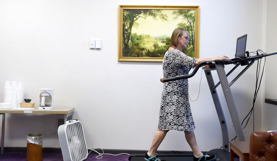 ADVANCE FOR WEEKEND EDITIONS AUG. 9-10 - In a July 29, 2014 photo, Ivetta Campbell, administrative services associate, walks on the treadmill at Lynchburg City Hall, in Lynchburg, Va. as part of the Work Healthy study.  Campbell walks on the treadmill for a half hour every day while being able to work remotely from a computer. (AP Photo/The News & Advance, Jill Nance)