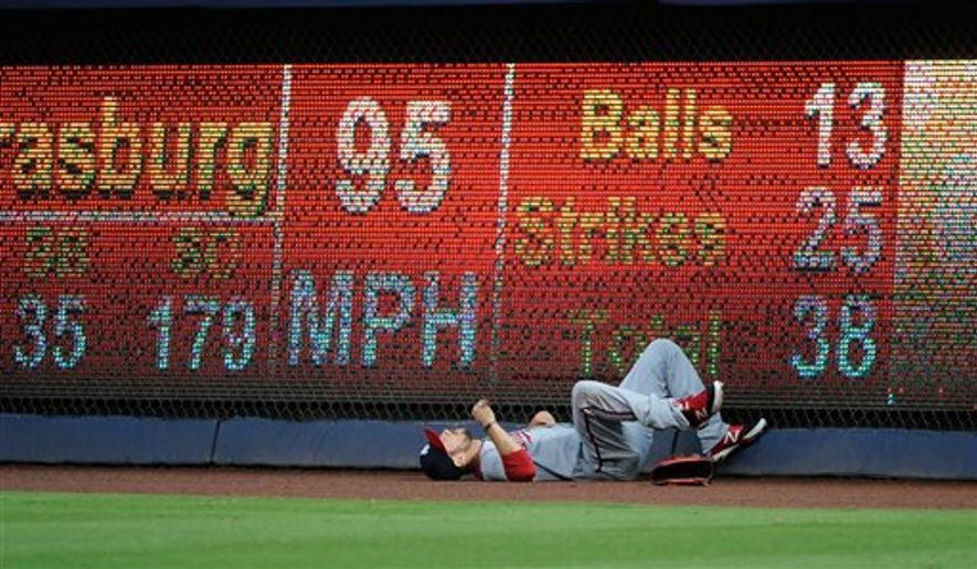 Washington Nationals right fielder Steven Souza falls to the warning track after slamming into the wall trying to field a two-run homer by Atlanta Braves' Freddie Freeman during the second inning of a baseball game Friday, Aug. 8, 2014, in Atlanta. (AP Photo/David Tulis)