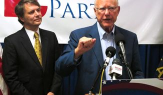 In this photo from Wednesday, Aug. 6, 2014, U.S. Sen. Pat Roberts, right, speaks at a rally of Kansas Republican activists as Lt. Gov. Jeff Colyer, left, watches, in Topeka, Kan. Roberts won his GOP primary race with only 48 percent of the vote but remains favored to win re-election. (AP Photo/John Hanna)