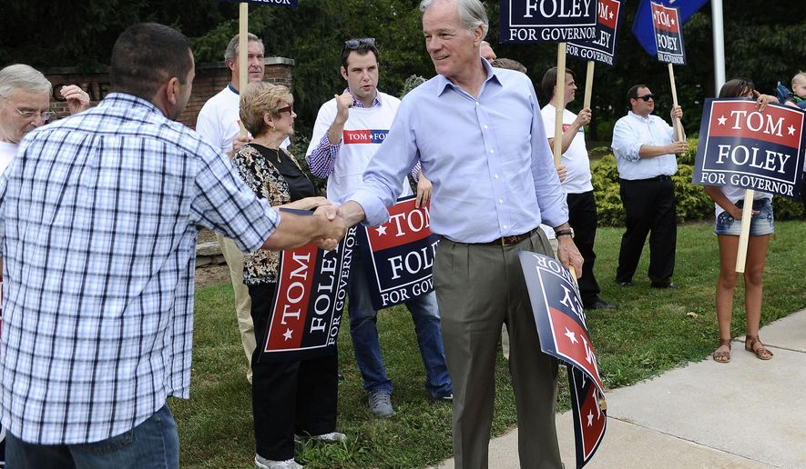 Republican candidate for Connecticut governor Tom Foley, center, shakes hands with supporter Ben Ancona as he greets commuters off an exit during rush hour,  Monday, Aug. 11, 2014, in West Hartford, Conn. Foley will face Republican John McKinney in Tuesday's primary. (AP Photo/Jessica Hill)