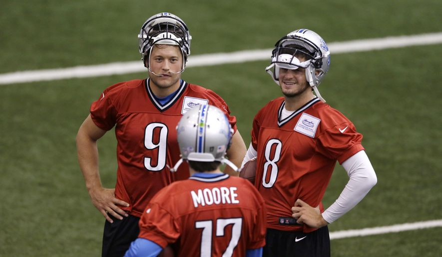Detroit Lions quarterbacks Matthew Stafford (9) and Dan Orlovsky (8) talk with quarterback Kellen Moore (17) during an NFL football training camp, Monday, Aug. 11, 2014, in Allen Park, Mich. (AP Photo/Carlos Osorio)