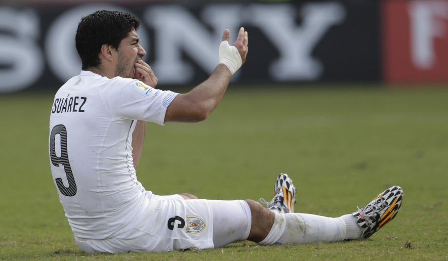 In this June 24, 2014 file photo, Uruguay's Luis Suarez holds his teeth after running into Italy's Giorgio Chiellini's shoulder during the group D World Cup soccer match between Italy and Uruguay at the Arena das Dunas in Natal, Brazil, Tuesday, June 24, 2014. After FIFA rejected Luis Suarez's appeal against his lengthy ban for biting Chiellini, Suarez appealed against the ban with the Court of Arbitration for Sport.(AP Photo/Petr David Josek, File)
