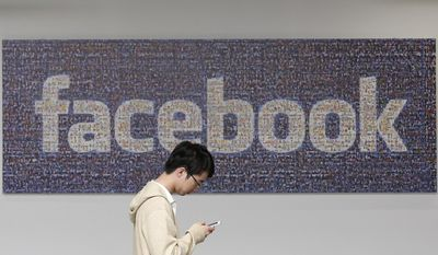 In this June 11, 2014 photo, a man walks past a Facebook sign in an office on the Facebook campus in Menlo Park, Calif. (AP Photo/Jeff Chiu, File)