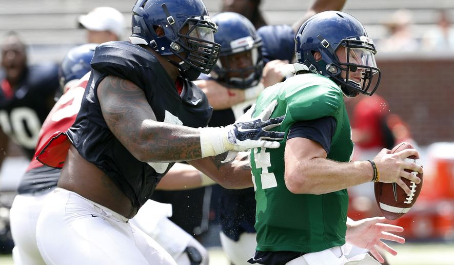 Mississippi defensive tackle Robert Nkemdiche, left, hauls down quarterback Bo Wallace during their final open NCAA college football practice, Saturday, Aug. 9, 2014, at Mississippi, in Oxford Miss. Players were involved in individual and team drills. (AP Photo/Rogelio V. Solis)